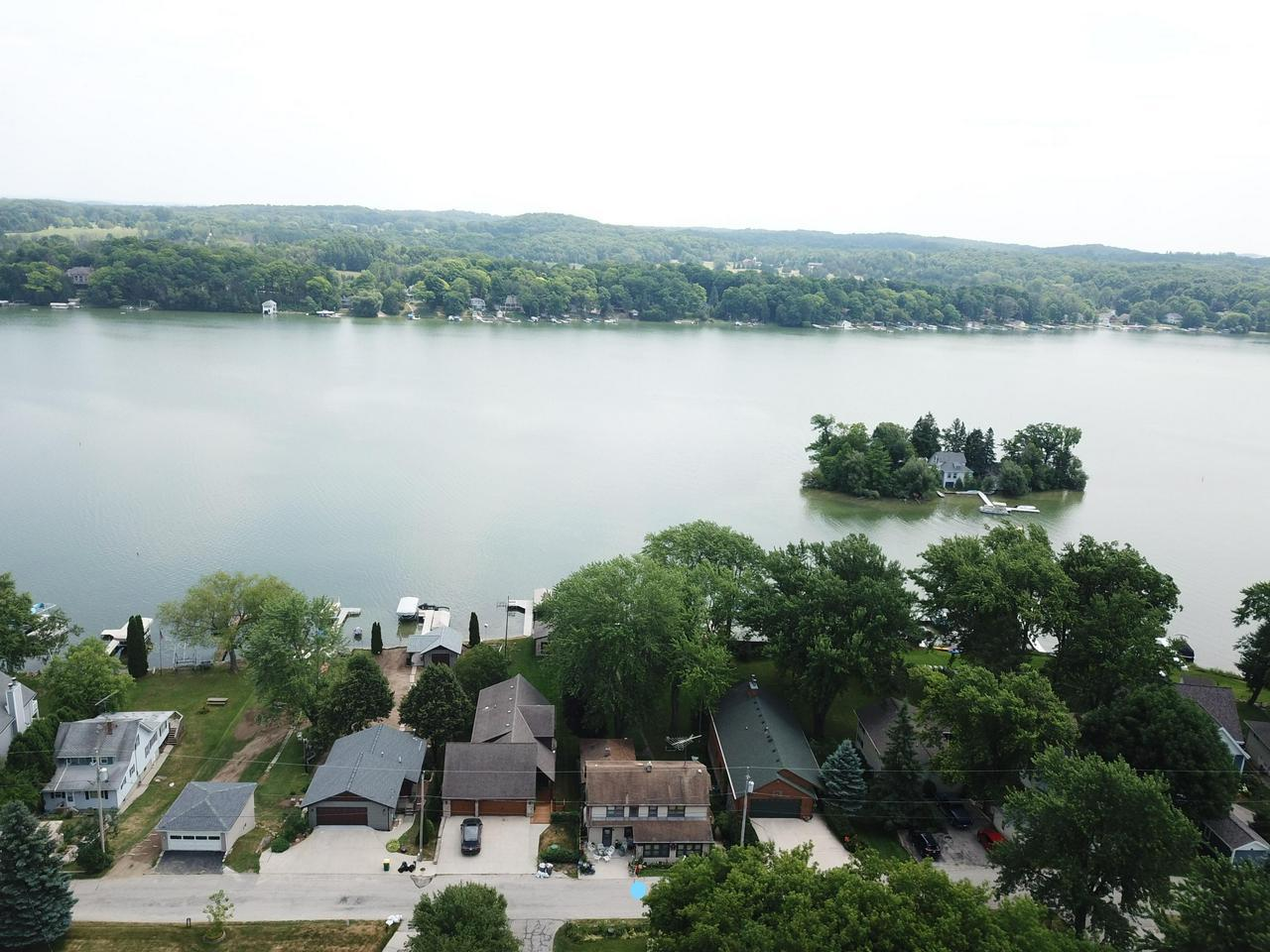 Fish, sail, swim, ski, boat or just simply enjoy life on this most prized 907ac, 105 ft deep, full recreational lake. Two(2) .23 ac lots for the price of one.  1-lake front lot w/50 Ft of prime, level, firm sandy bottomed swimming beach and 1-60' wide back lot for garden, garage and extra parking. This 2200+sq ft 4 bedroom, 2 bath home with an extra detached seasonal guest cottage is sandwiched between 2 beautifully updated homes. Both piers pictured are included in the sale. Beautifully preserved orig. woodwork throughout with lots of natural light and lake views.