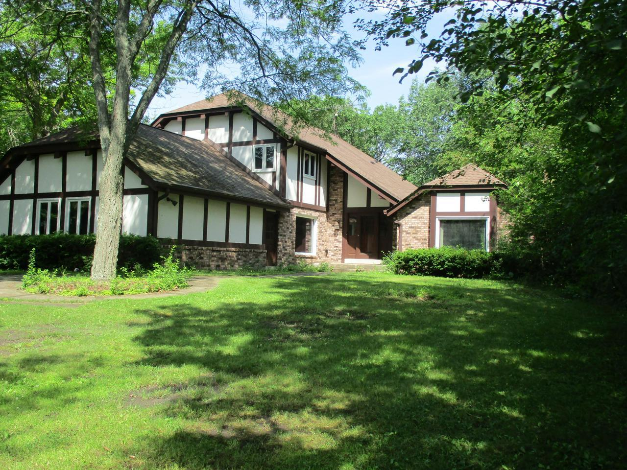 Updated Tudor on private, wooded 1 acre with large deck to entertain & enjoy nature. Kitchen and main flr laundry beautifully updated in 2017. Stone fireplace in freshly painted FMR & HWF updated 2016. 2nd FP in elegant LVR with french drs & HWF. Formal DR w/ HWF's has large window overlooking front yard. Huge main floor den w/ BIBC. Large MBR offers 2 WIC's & tiled ba with shower. Main ba updated 2013 and powder room 2014. Upper bedrooms are generous size. Extra spacious LL has partially finished rec rm. See Sellers' list of updates for information on all the updates done.