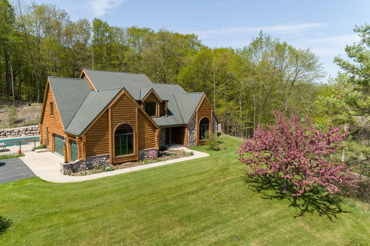Welcome home to your private retreat, nestled on 12.5 acres! This gorgeous log home has many updates including a chef's eat-in KIT with top of the line KitchenAid appliances, knotty hickory cabinets, leather-finished granite and a concrete farmhouse sink. 1st flr: family room with vaulted ceiling and NFP, master suite, dining room, laundry and large office. 2nd flr: three more bdrms and large loft with sliding doors to deck. Entertainer's LL: movie room, gas fireplace, wetbar, sauna and workout room. Amazing property w/ in-ground pool, 20x40 outbuilding/workshop, 70x40 horse barn w/ 6 stalls!