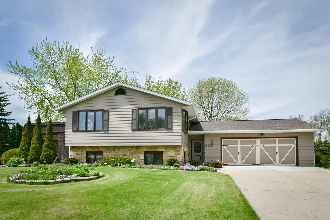 Great home at a Great price. this custom built Open Concept style 4br/2ba gem w/full walk-out lower is nestled on a gorgeous park-like setting oversized .548 ac village lot. Pride of Ownership abounds w/updates galore, Roof/2007,windows/2013,remodeled bath w/heated flr/2006,house painted/2010,kitchen tile/corian countertop/2010,H2O softener/2013,stained deck/2013,H2O heater/2012,patio drs/2016 & more. Great Rm w/vaulted ceiling,dining area w/patio dr to cozy deck.2 bdrms in lower w/egress windows. Rec Rm w/Gas FP & patio drs to patio overlooking a private yard w/perennials, fruit trees. WOW!